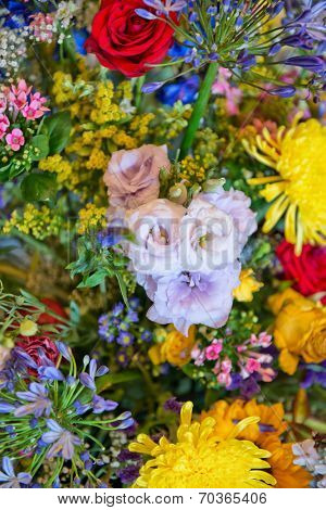 Colorful vivid background texture of a wide assortment of summer flowers in a large bouquet in vertical format