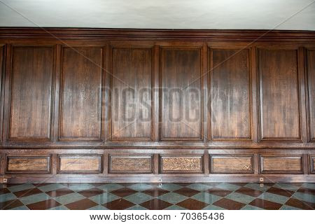 Old medieval wood paneling covering a wall in a historical country house with a diamond pattern marble floor, background image with nobody