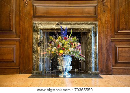 Flower arrangement of colorful summer blooms in a blue and white pottery urn in a historical marble fireplace with wood paneling on the walls