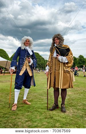 HAMPTON COURT, UK - AUGUST 03, 2014 - Two men dressed in historical Baroque costume during an outdoor re-enactment standing in a field with tents posing and looking at the camera on August 03, 2014