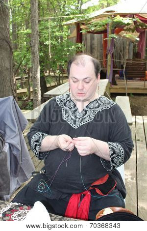 MUSKOGEE, OK - MAY 24: A man shows off craft of lace making at the Oklahoma 19th annual Renaissance Festival on May 24, 2014 at the Castle of Muskogee in Muskogee, OK