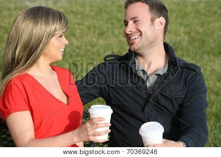 Young couple sitting on the grass drinking coffee