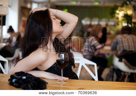 Young beautiful trendy woman in the bar. Beautiful Asian girl in a pub. Woman with alcohol.