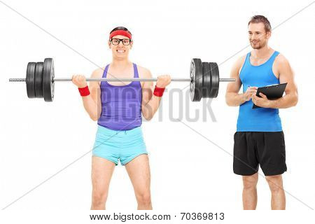 Nerdy guy lifting weight and a fitness coach standing beside him isolated on white background