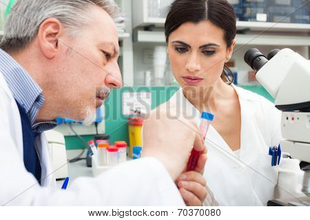 Doctors examining a blood sample in a laboratory