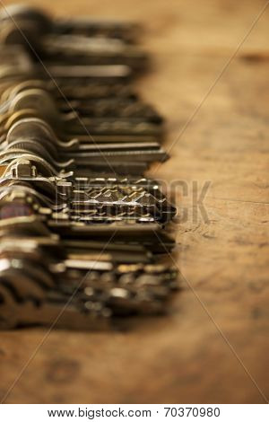 Many old keys, aligned on a well used old wooden desk. Shallow depth of field.