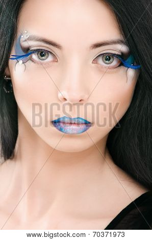 Beautiful female face with blue fashion make-up