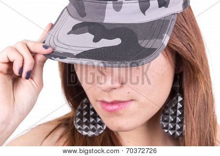 Face closeup of young girl holding military cap with hand