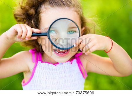 Little girl is looking through magnifier, outdoor shoot