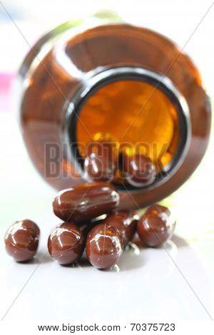 Brown Pills And Pill Bottle.
