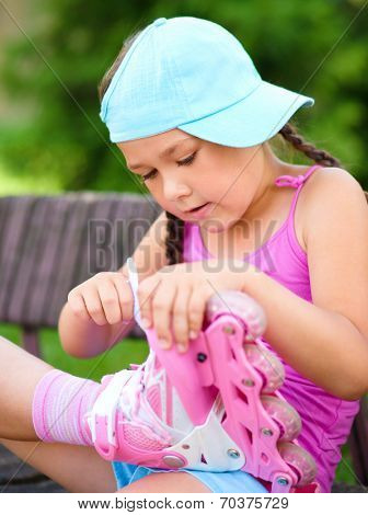 Little girl is wearing roller-blades in city park