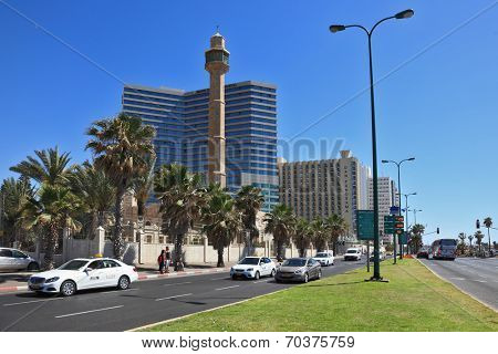 TEL AVIV, ISRAEL - MAY 2, 2014: Spring Tel Aviv promenade. Arab mosque and minaret on the background of high-rise hotel