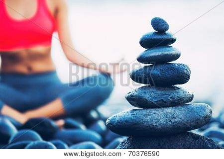 Stack of Round Smooth Stones on the Seashore, Woman Practicing Yoga in the background