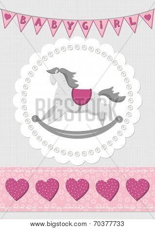 baby girl toy animal rocking horse on white doily with flag banner and ribbon