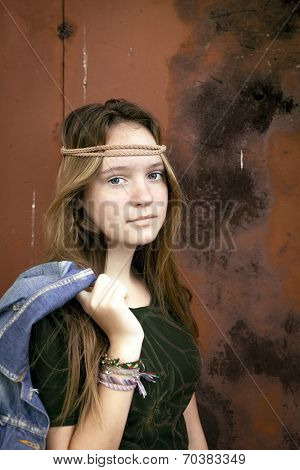 Cute young hippy girl with a denim jacket, and a red metal wall in the background.