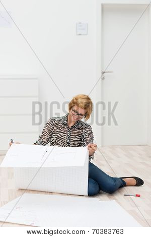 Woman Looking At Building Plans In Her New House
