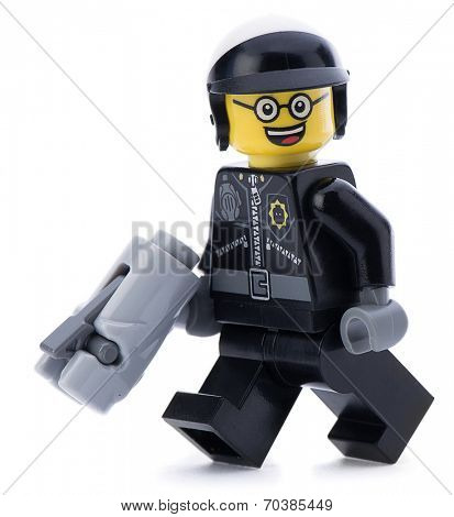 Ankara, Turkey - March 15, 2014 : Lego movie minifigure character good cop with gun walking isolated on white background.
