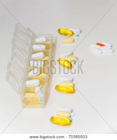 Pills And Pill Container On White Counter