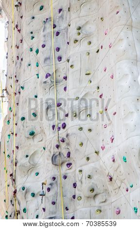 Purple And Green Handholds On Climbing Wall
