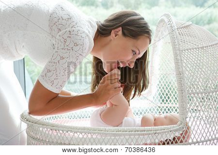 Attractive Mother Playing With Baby In Cot