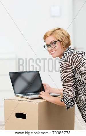 Young Woman Using A Laptop On A Cardboard Box