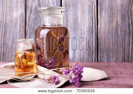 Bottles of herbal tincture and brunch of flowers on a napkin on a wooden table in front of wooden wall