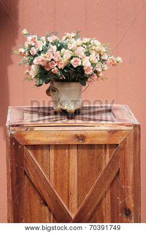 Pink Flowers In Jardiniere On The Brown Wooden Box.