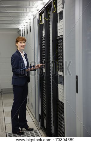 Technician working on servers using tablet pc in large data center