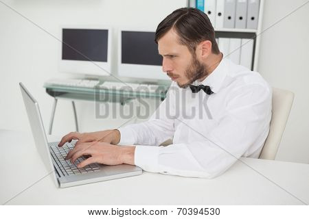 Nerdy businessman working on laptop at desk in his office