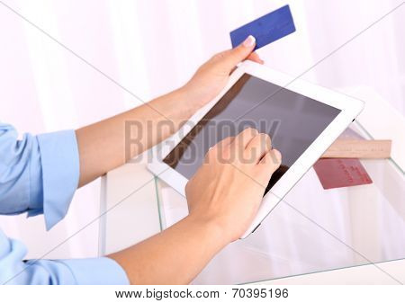Woman using digital tablet and holding credit card in her hand, close-up. On-line shopping concept