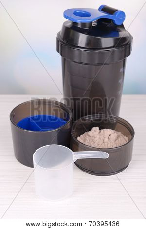 Whey protein powder and plastic shaker on table on bright background