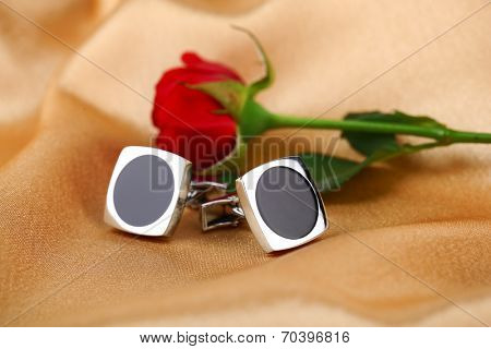 Pair of cuff links with red rose on light silk fabric background