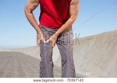 Active senior man touching his injured thigh on a sunny day