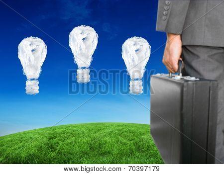 Businessman holding briefcase against cloud light bulbs