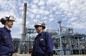 stock photo of factory-worker  - two oil engineers talking with refinery in background - JPG