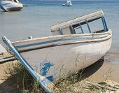 stock photo of derelict  - Old derelict small boat abandoned on beach by coast - JPG