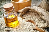 stock photo of sesame seed  - sesame seeds in sack and bottle of oil on wooden rustic table - JPG