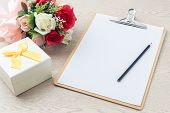 image of beside  - Wooden Clipboard attach planning paper with pencil on top beside rose bouquet gift box on table - JPG