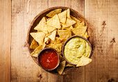 foto of nachos  - Fresh salsa and guacamole dips with nachos chips on wooden background - JPG
