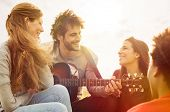 stock photo of guitar  - Happy group of friends enjoying the summer outdoor playing guitar and singing together - JPG