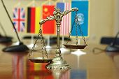 stock photo of justice law  - Decorative Scales of Justice with blurred National flag of different countries - JPG