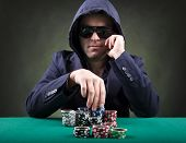 stock photo of spade  - Thoughtful poker player on black background - JPG