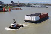 stock photo of barge  - A tug boat towing a barge up the Fraser River near the Oak Street bridge - JPG
