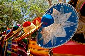 stock photo of sombrero  - colorful Mexican sombreros and ponchos lined up outdoors - JPG