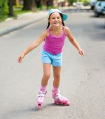 stock photo of roller-skating  - Happy little girl is skating on rollers - JPG