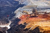 stock photo of open-pit mine  - open coal mining pit with heavy machinery - JPG