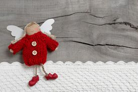 stock photo of christmas angel  - Red christmas or guardian angel on grey wooden background for a greeting card - JPG