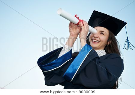 Happy Graduate Girl Looking Through Diploma