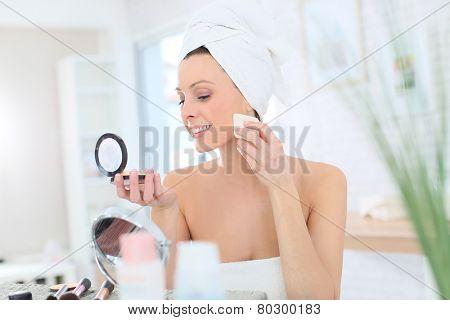 Beautiful woman putting makeup on