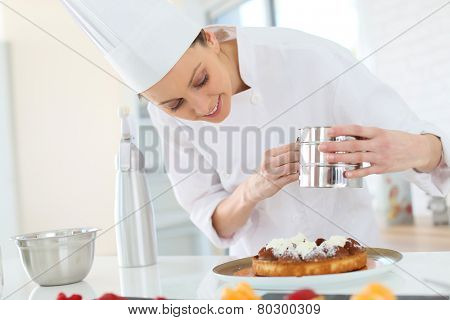 Pastry cook spreading icing sugar on tart